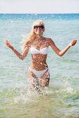 Jolie femme blonde en bikini blanc dans l'eau éclabousse en mer — Photo