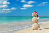 Sandy snowman in santa hat. Holiday concept for New Years and Ch — Stock Photo