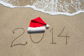 Happy new year 2014 with christmas hat on sandy beach - holiday — Stock Photo