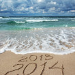Happy New Year 2014 wash away 2013 concept on sea beach — Photo