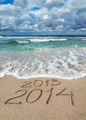 Happy New Year 2014 wash away 2013 concept on sea beach — Stock Photo