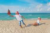 Young couple running at sea beach in santa hats with sled and ch — Stock Photo