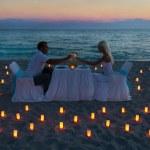 Lovers couple share a romantic dinner on sea beach — Stock Photo
