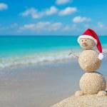 Sandy snowman in santa hat sunbathing in beach lounge. Holiday c — Stock Photo #34005355