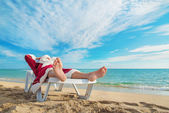 Sunbathing Santa Claus relaxing in bedstone — Stock Photo