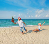 Young couple running at sea beach in santa hats — Stock Photo