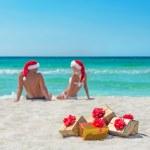 Young couple in santa hats at sea beach — Stock Photo