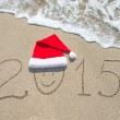 Happy new year 2015 with smiley face in santa hat on sandy beach — Stock Photo #35813537