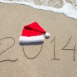 Happy new year 2014 with santa hat on sea beach — Stock Photo #35813539