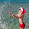 Beautiful blonde woman in red christmas hat on sea beach — Stock Photo #35813653