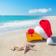 Santa Claus hat and christmas gift box on the seashore with — Stock Photo