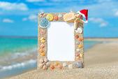 Sea shells frame with christmas hat against sea beach — Stock Photo