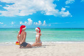 Man in santa hat giving a present to his girlfriend — Stok fotoğraf