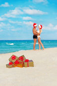 Hugging lovers couple in santa hats at sea beach — Stock Photo