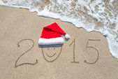 Happy new year 2015 with smiley face in santa hat on sandy beach — Stock Photo