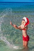 Deniz sahilinde kırmızı Noel şapkalı güzel sarışın kadın — Stok fotoğraf