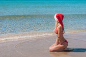 Beautiful blonde woman in red christmas hat on sea beach. — Stock Photo