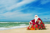 Santa Claus at sea beach with many gifts — Stock Photo