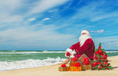 Santa Claus at sea beach with many gifts — Stock Photo