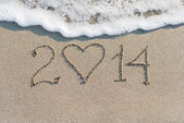 Happy New Year 2014 on the sea sandy beach with heart — Stock Photo