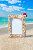 Sea shells frame with christmas hat against sea beach — Stock Photo