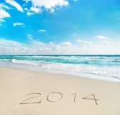 Inscription 2014 on sea sand beach with the sun rays — Stock Photo