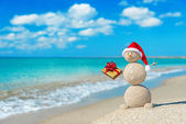 Smiley sandy snowman at beach in christmas hat — Stock Photo