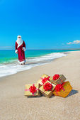 Santa Claus with many golden gifts relaxing on sea beach — Stock Photo