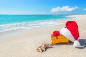 圣诞老人的帽子和圣诞礼品盒在与海的海滩上 — 图库照片