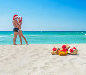 Kissing lovers couple in santa hats at sea beach — Stock Photo