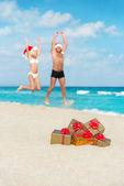 Happy lovers couple in santa hats jumping at sea beach — Stock Photo