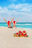 Happy couple in santa hats hands up at sea beach — Stock Photo