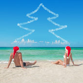 Lovers couple in santa hats at tropical sandy beach - christmas — Stock Photo