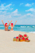 Happy couple in santa hats hands up at sea beach with christmas — Stock Photo