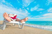 Sunbathing Santa Claus relaxing in bedstone on beach - Christmas — Stock Photo