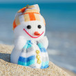 Smiley toy snowman at sea beach. Holiday concept for New Years and Christmas Cards. — Stock Photo