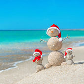 Snowmans family at sea beach in santa hat. — Stock Photo