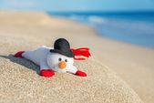 Smiley toy christmas snowman at hot sea beach. — Stock Photo