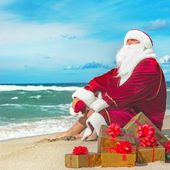 Santa Claus with many golden gifts relaxing at beach — Stock Photo
