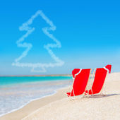 Santa hat on chaise longues at white sand beach against the sea — Stock Photo