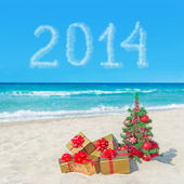 Christmas tree and gift boxes on sea beach. Concept for New Year — Stock Photo