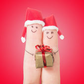Fingers faces in Santa hats with gift box. Happy couple concept — Stock Photo