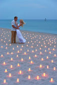Proposal at sea beach in candles against sunset — Stock Photo