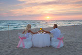 Couple at beach romantic dinner with candles — Stok fotoğraf