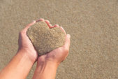 Hands holding a sand in form of heart — Stock Photo