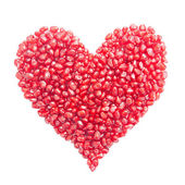 Heart-shaped pomegranate seeds isolated on white — Stock fotografie