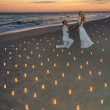 Couple at sea beach in candles against sunset — Stock Photo #45402591