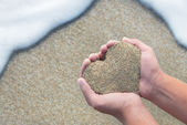Hands holding a sand in form of the heart - beach concept — Stock Photo