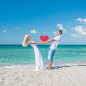 Casal na praia do mar ensolarado com coração vermelho — Fotografia Stock
