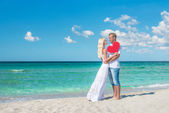 Loving couple at sunny sea beach with red heart — Stock Photo